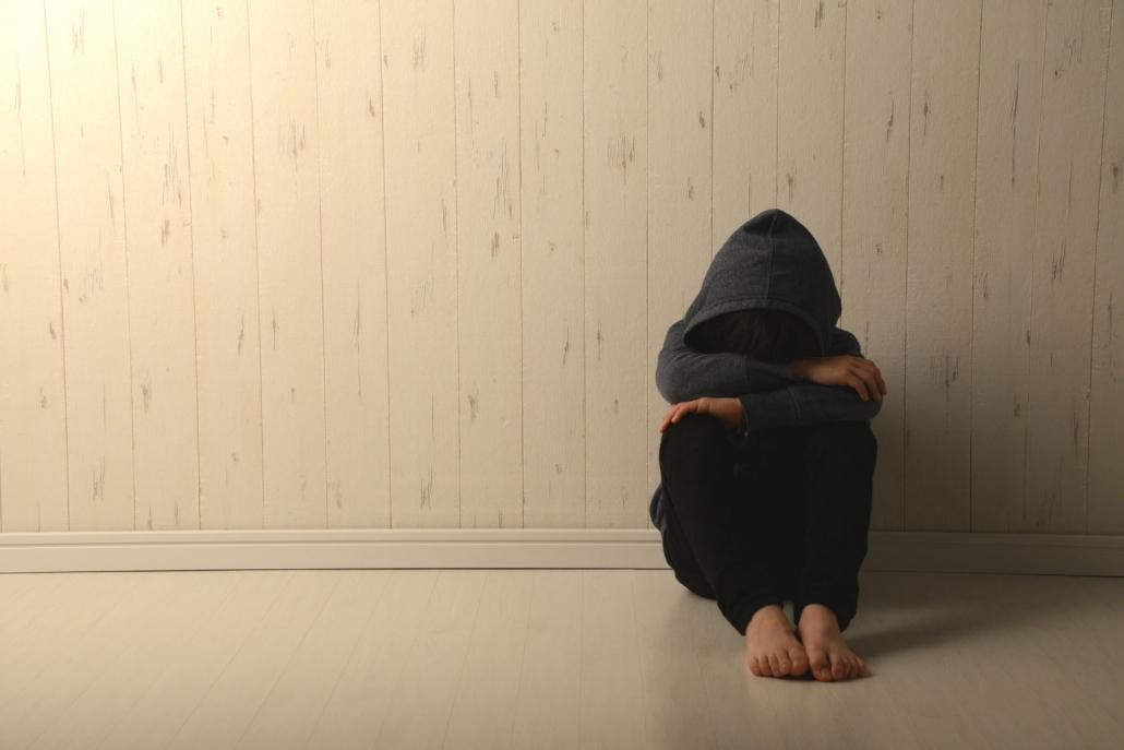 Ein Jugendlicher kauert mit angezogenen Beinen und den Kopf in die Arme gelegt an einer Wand