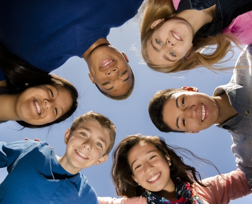 Multi-ethnic group of teenage friends hang out, huddle together with arms around each other outdoors. Blue sky background.